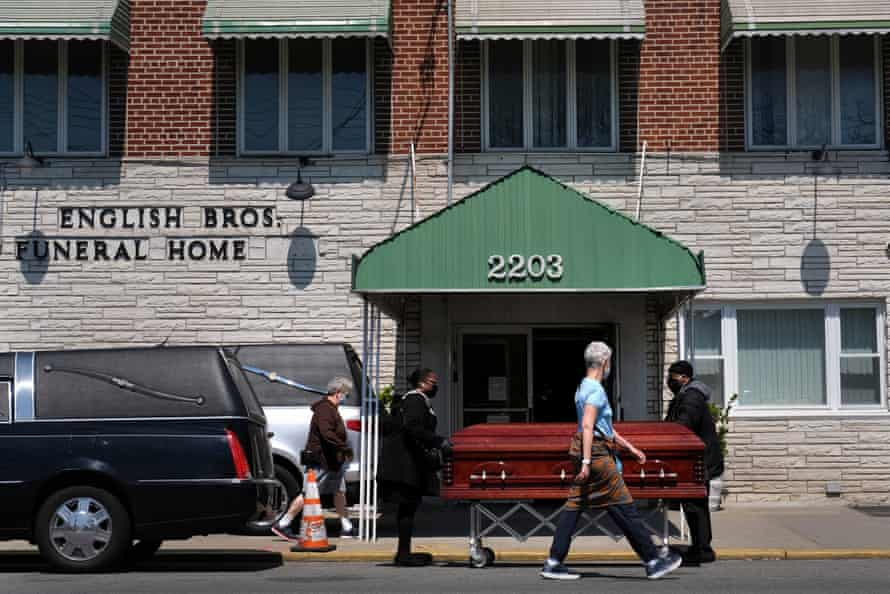 Pedestrians walk past the English Bros Funeral Home as a casket is unloaded in the Brooklyn borough of New York.