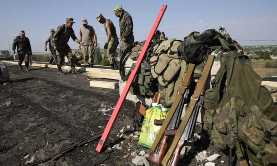 Ukrainian servicemen repair the roof of a kindergarten in the town of Luganskoye in the Donetsk region.
