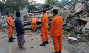 Rescuers inspect collapsed houses in North Lombok.