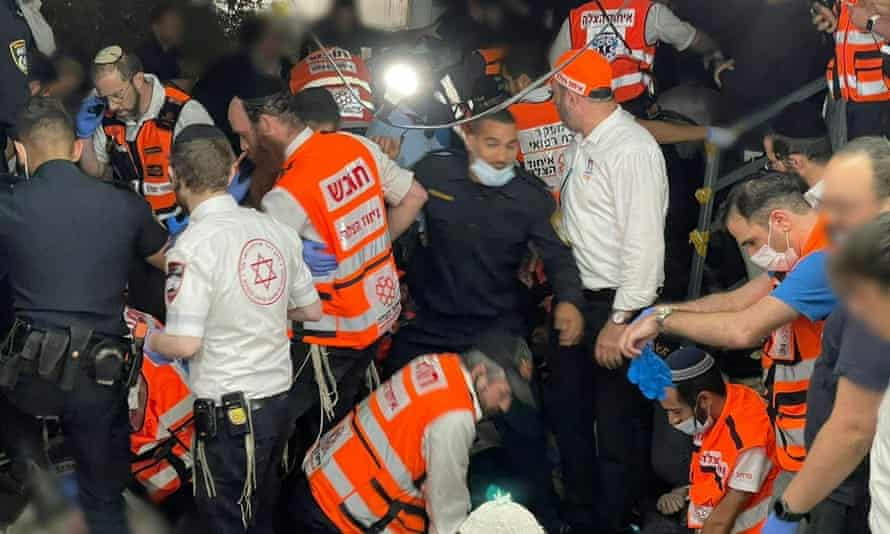 Emergency personnel assist people after dozens were killed and others injured after a grandstand collapsed in Mount Meron