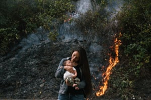 Crissy Robbins, daughter of Cultural Fire Management Council president Margo Robbins, holds her son Kenneth Koy-o-woh in front of the prescribed burn in Weithpec, California.
