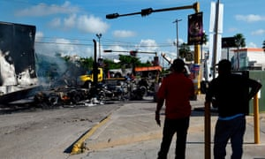 Men look at burnt vehicles after heavily armed gunmen waged an all-out battle against Mexican security forces in Culiacan, Sinaloa state, Mexico, on Friday.