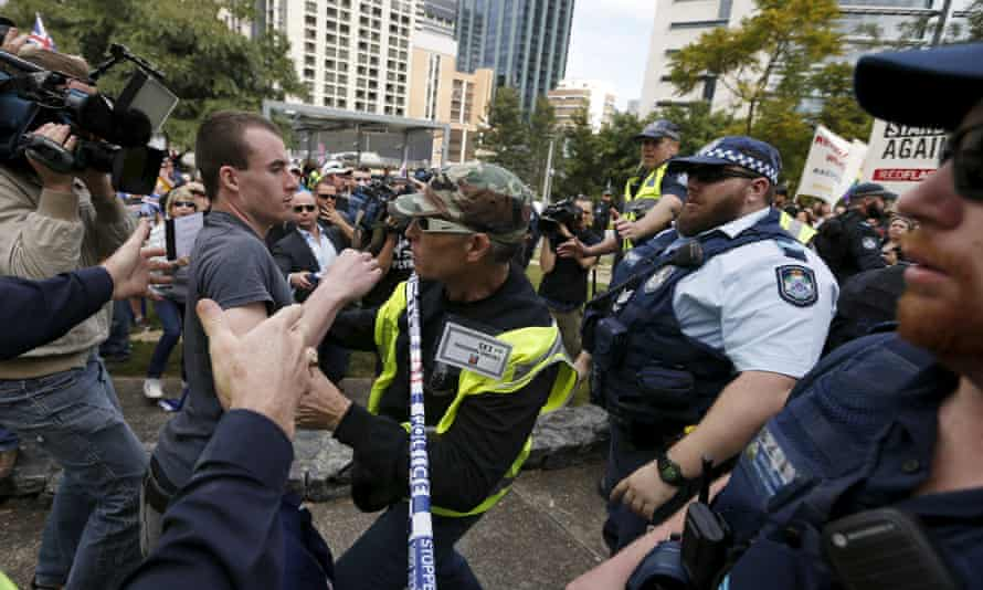 A Reclaim Australia supporter is held back by a volunteer as he lunges across police tape during a rally in Brisbane on 19 July. ,