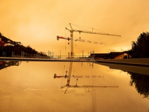 Construction cranes are reflected in a pool of water under a yellow-coloured sky in Bramois, Switzerland.