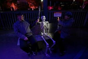 A woman takes a photo of a fake skeleton sitting on a bench