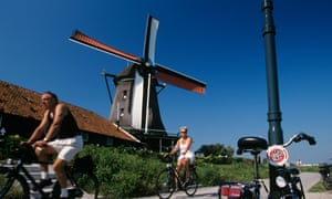 Cyclists past windmill