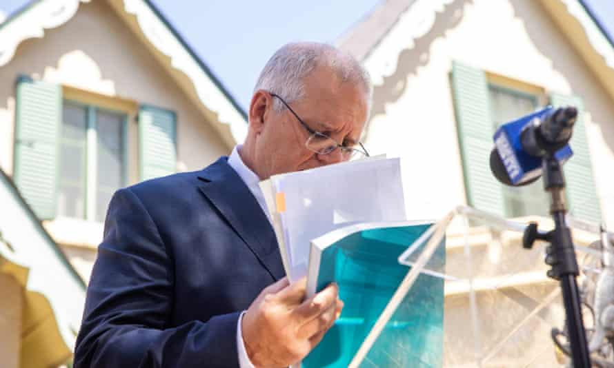 Australian prime minister Scott Morrison looks through documents as he delivers the aged care royal commission report on 1 March 2021