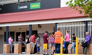 People are seen in a queue outside a Centrelink office in Brisbane, March 24, 2020.