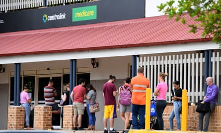 People are seen in a long queue outside a Centrelink office in Brisbane on Tuesday in the wake of business closures due to the coronavirus pandemic.