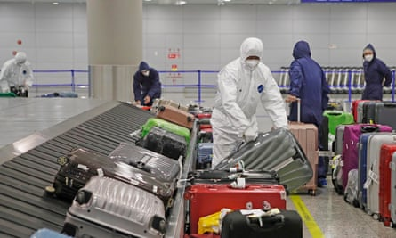 Workers wearing protective suits at Shanghai Pudong International Airport