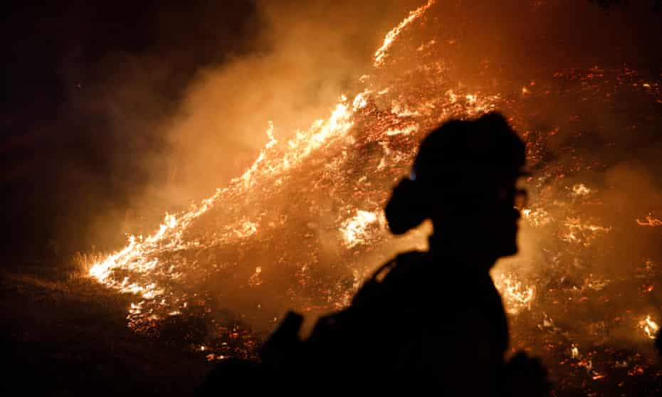 Firefighters stand watch by a fire line as the Kincade fire burns on the outskirts of Santa Rosa, California, on Monday.