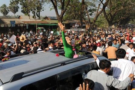 Aung San Suu Kyi waves as she crosses a crowd of supporters while arriving for a political rally in Pathein in 2012