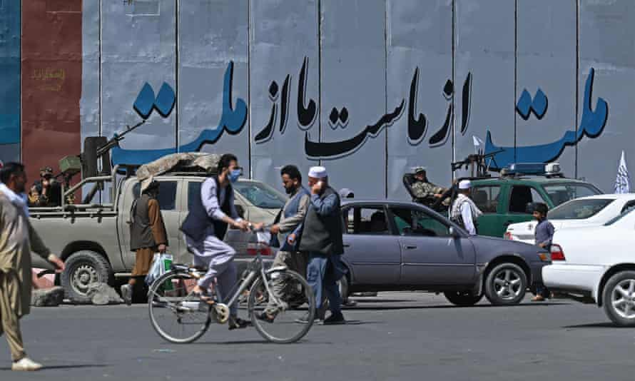 People move past Taliban fighters sitting in their vehicles along a street in Kabul