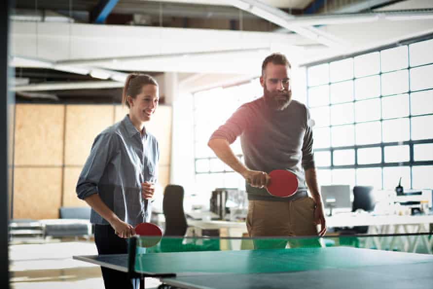 Office workers playing table tennis