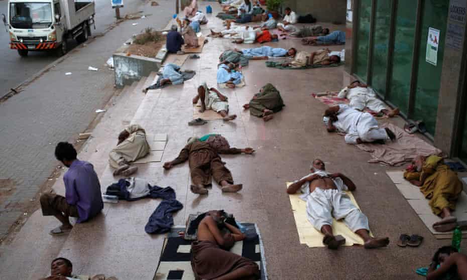 Residents sleep on the pavement in Karachi