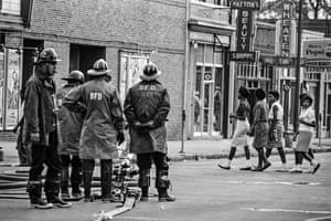 Members of the Birmingham Fire Department watch a group of girls cross the street.