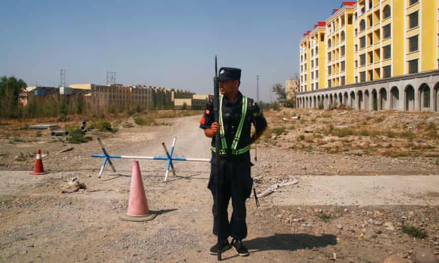 A Chinese police officer takes his position by the road near what is officially called a vocational education centre in Yining in Xinjiang