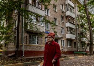 An elderly resident walks past a Khrushchevka apartment block
