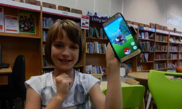 Young girl sitting in library holds up phone displaying Pokemon Go game.