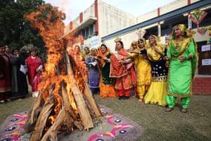 Amritsar, India: students and teachers wearing traditional Punjabi attire put peanuts and popcorn into a bonfire as they celebrate Lohri festival