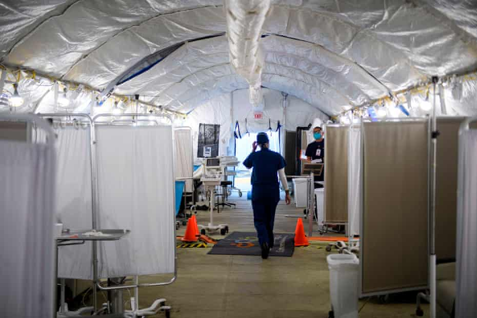 Kennoka Williamson, a registered nurse, attends to patients in a Covid-19 triage area set up in a field hospital tent outside the hospital.
