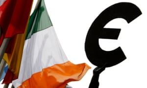 An Irish flag flies next to a symbol of the euro currency at the entrance of the European Parliament in Brussels