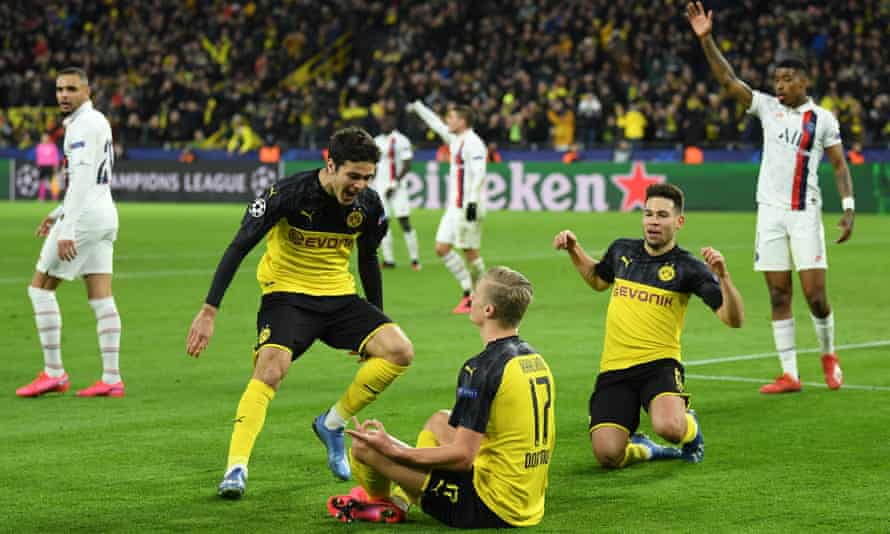 Erling Haaland celebrates with Gio Reyna and Raphaël Guerreiro after giving Dortmund the lead.