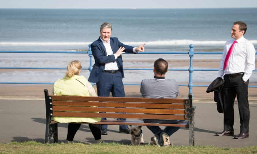 Keir Starmer and Dr Paul Williams talk to two people sitting on a bench by the sea.