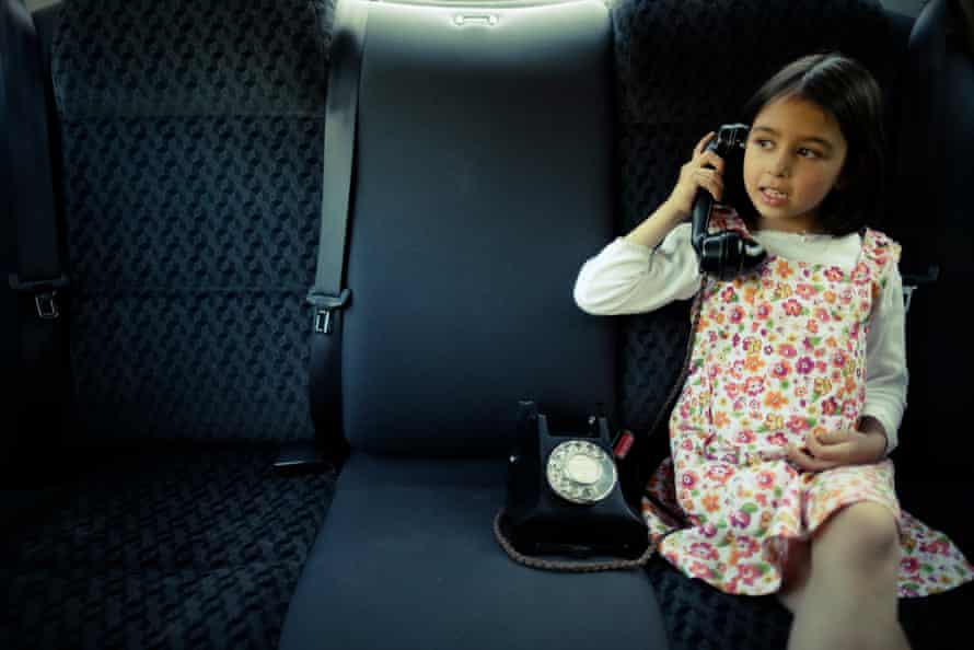 Car phoneGirl using a vintage Bakelite phone in the back seat of a car.