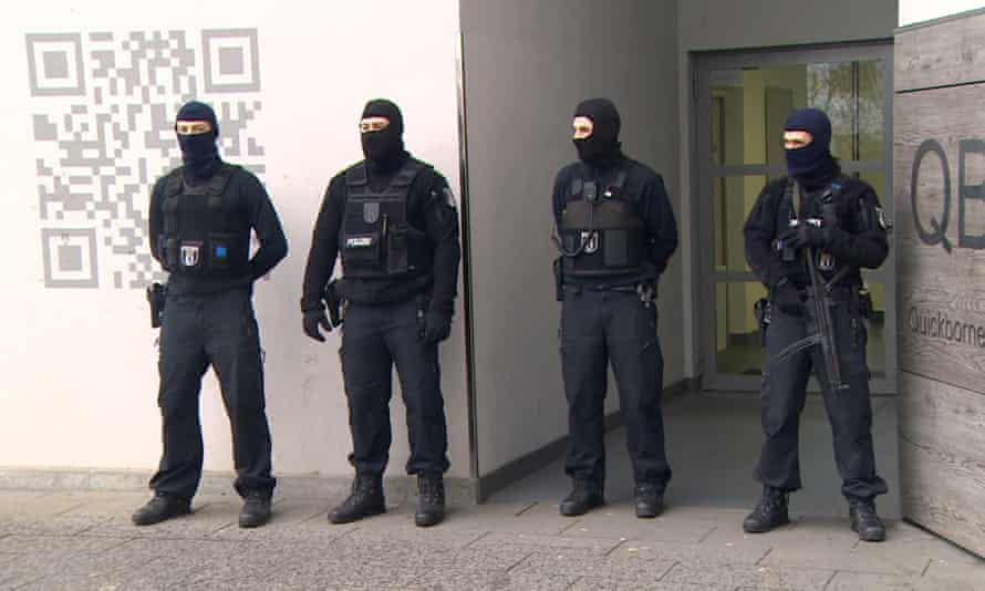 Police guard a residential building in Berlin after a raid in connection with the Fussilet 33 mosque