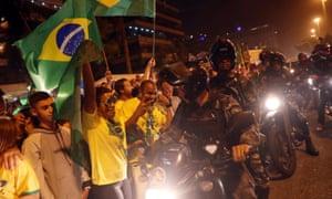Police ride past supporters of Jair Bolsonaro in Rio de Janeiro.
