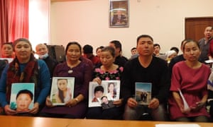 In this December image, Kazakh relatives of people missing in Xinjiang hold up photos of their loved ones.