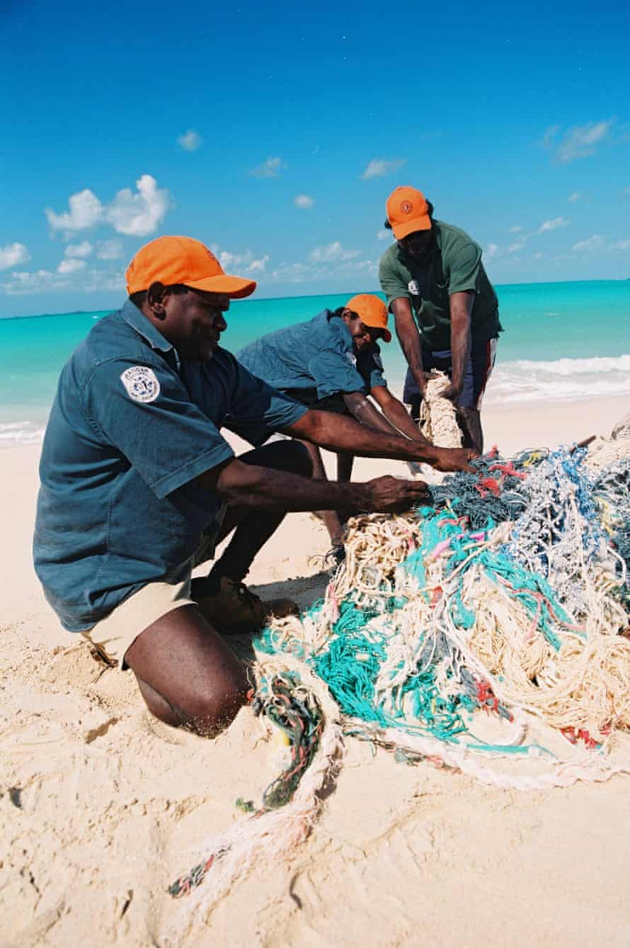 Rangers from the Dhimurru IPA clear a ghost net from a beach in north-east Arnhem Land.
