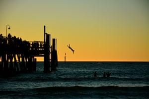 Sunset diving from the jetty at Glenelg beach, Adelaide, Australia