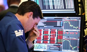 A trader on the New York Stock Exchange puts a hand over his eyes