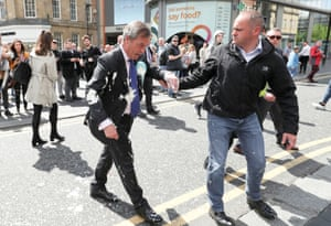 Newcastle, England Brexit party leader Nigel Farage is assisted after being hit with a milkshake while arriving for a campaign event