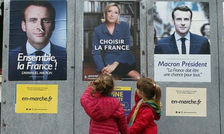 Children walk past candidate posters in Ossès, south-western France, on the final weekday of campaigning.