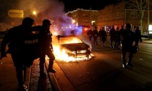 Police officers walk by a burning police car in Ferguson, Missouri.