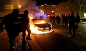 Police officers walk past a burning police car in Ferguson
