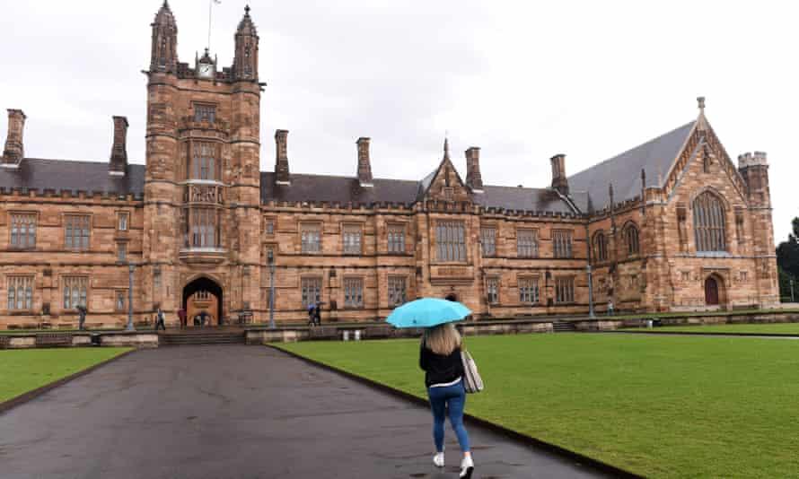 woman with umbrella walks towards the Sydney uni quadrangle