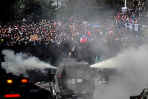 Santiago, ChileRiot police try to disperse demonstrators during the fifth straight day of street violence which erupted over a now suspended hike in metro ticket prices