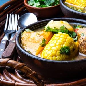 Latin American chilean food. Traditional chilean cazuela de cerdo with chuchoca. Pork soup with potatoes, pumpkin. corn served in clay bowl