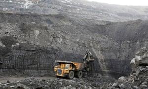 A machine loads dump-body truck with coal at Chernigovsky opencast colliery in Siberia, Russia.