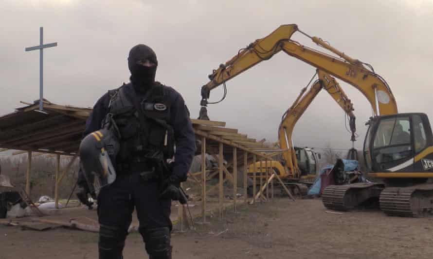 A policeman stands guard as a digger destroys a church at a migrant camp in Calais on 1 February