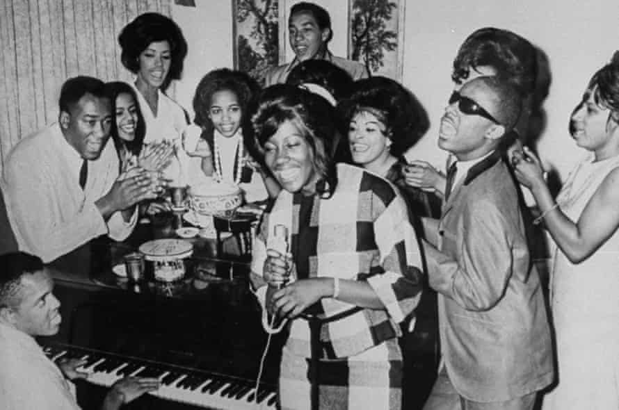 'We're always gonna make quality records' … Berry Gordy (bottom left) playing piano for a group including Smokey Robinson (at back) and Stevie Wonder (second right).