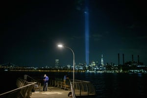 A fisherman in Brooklyn prepares his line on a pier before the Tribute in Light public art installation commemorating the 9/11 2001 terrorist attacks, shining up from the city skyline of lower Manhattan