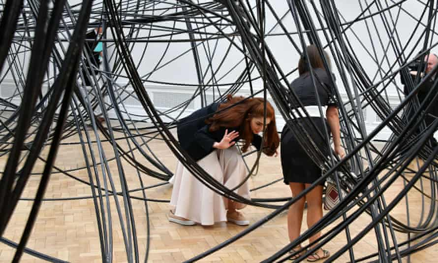 Visitors clamber through Clearing by Antony Gormley at the Royal Academy in London.
