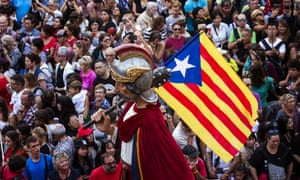 A statue holding an independence flag is carried through Plaça Sant Jaum, Barcelona, during a pro-referendum rally.