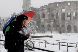 A woman shelters from the snow as she walks past The Colosseum on February 26, in Rome, Italy. The 'Beast from the East', an arctic storm set record low temperatures across much of Europe, with Rome seeing it's first snowfall in years.