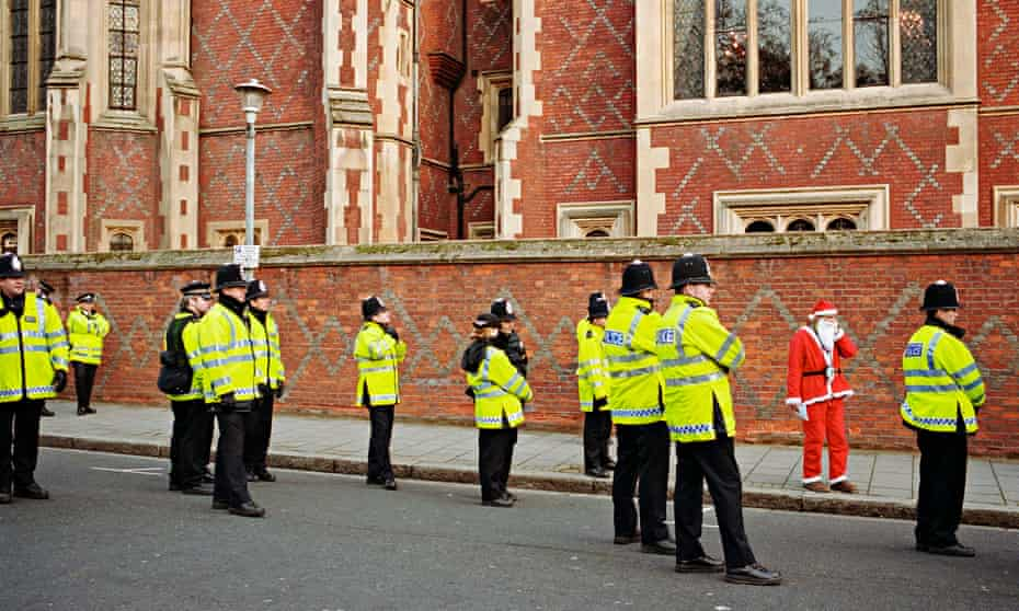 A lone Santa Claus among a group of police officers.
